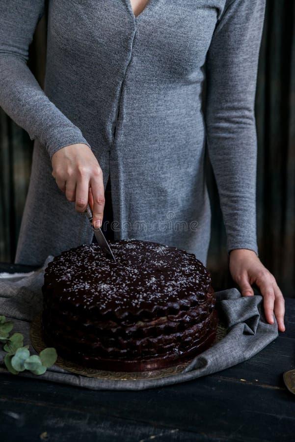 De vrouw snijdt dichte chocoladecake Donkere tonen stock fotografie