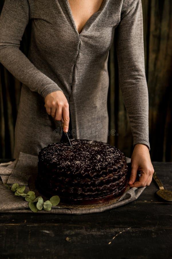 De vrouw snijdt dichte chocoladecake Donkere tonen royalty-vrije stock foto's