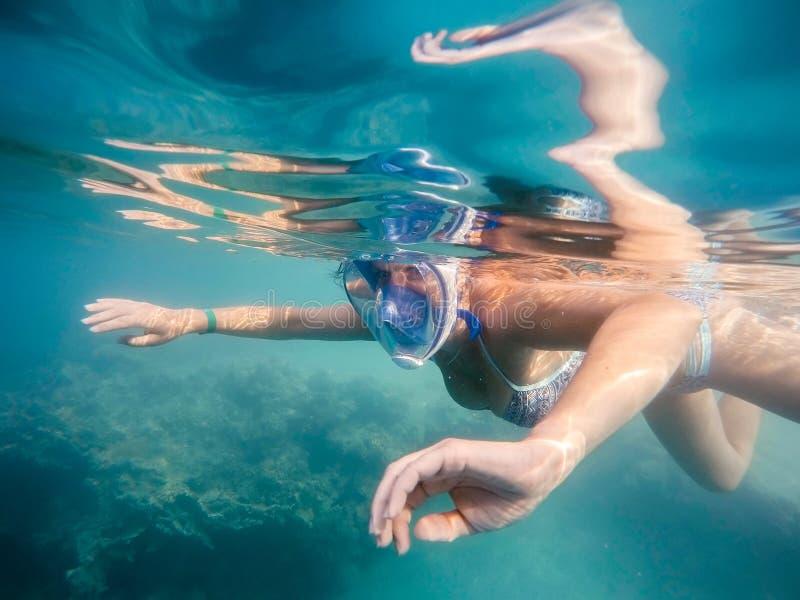 De vrouw snorkelt in ondiep water stock foto
