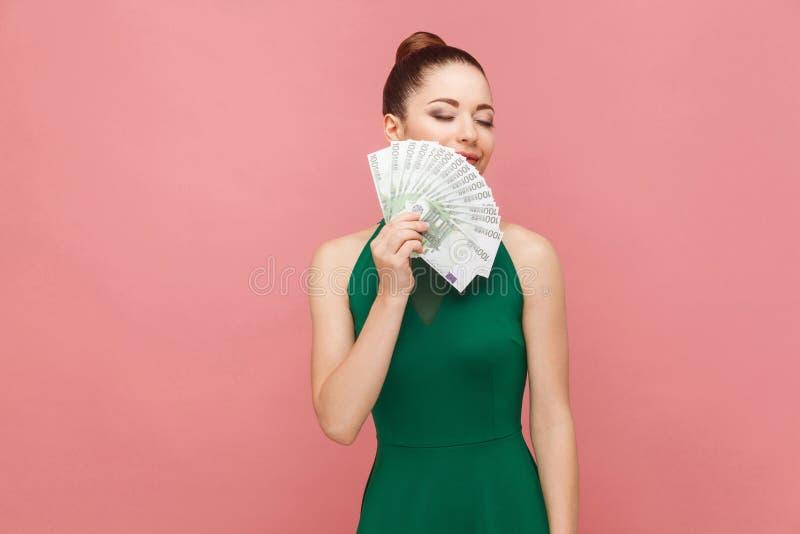 De vrouw snuift geld en het glimlachen stock foto