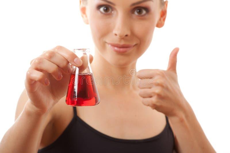 De vrouw in sportenkostuum houdt fles met rode vloeistof royalty-vrije stock afbeeldingen