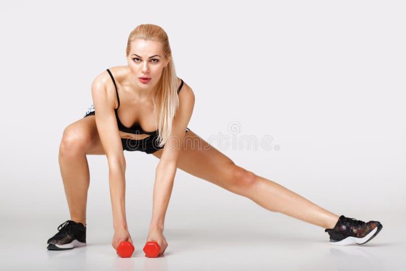 De vrouw in sportkleding doet oefeningen stock fotografie
