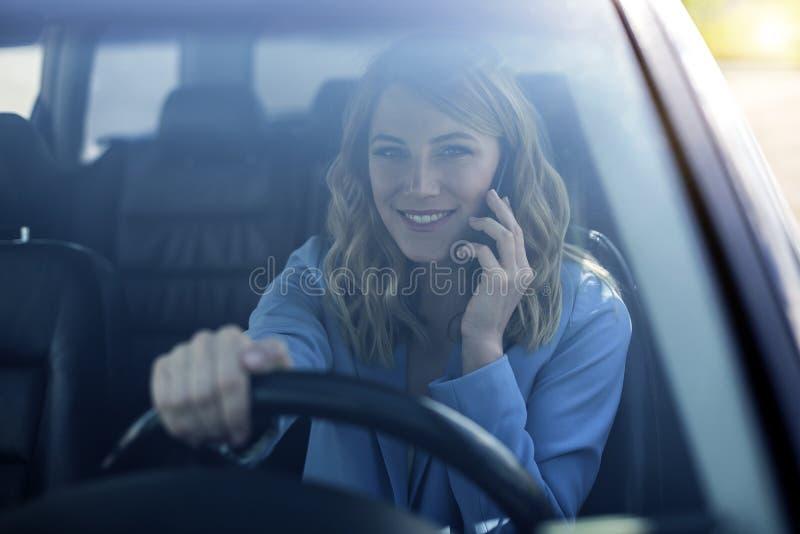 De vrouw spreekt op de telefoon in de auto royalty-vrije stock afbeeldingen