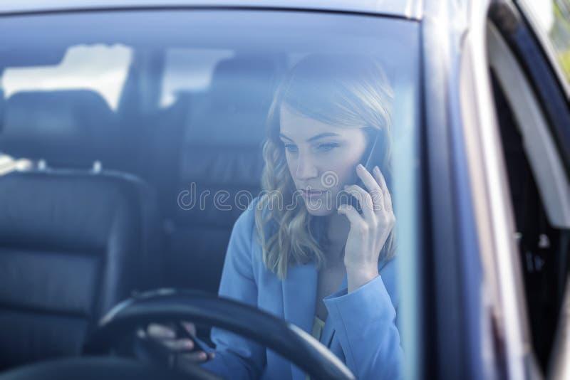 De vrouw spreekt op de telefoon in de auto stock fotografie