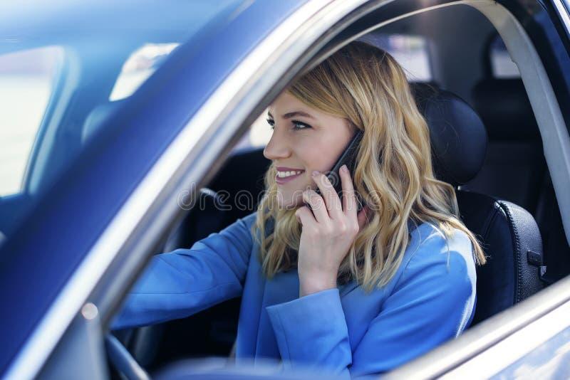 De vrouw spreekt op de telefoon in de auto royalty-vrije stock fotografie