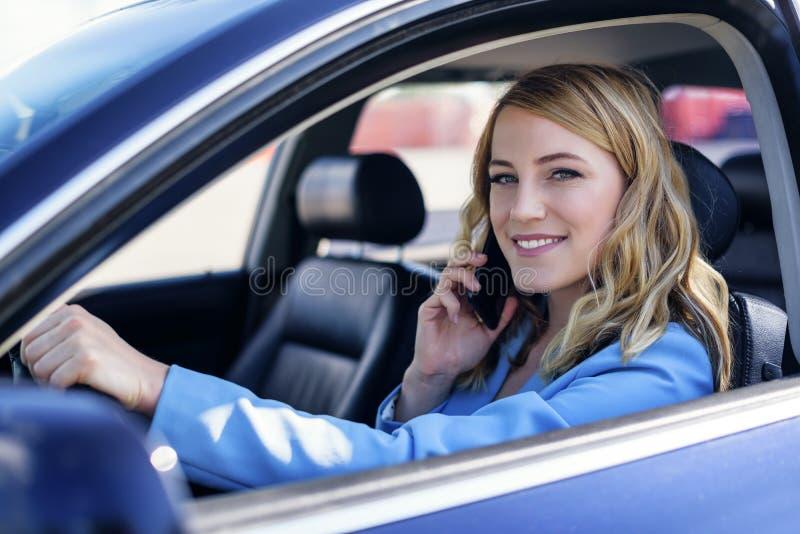 De vrouw spreekt op de telefoon in de auto stock foto's