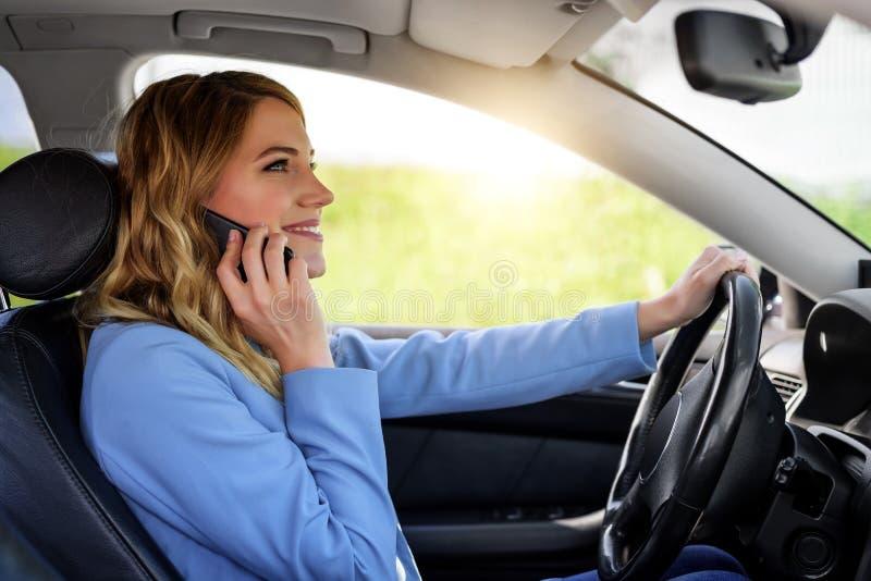 De vrouw spreekt op de telefoon in de auto stock afbeeldingen