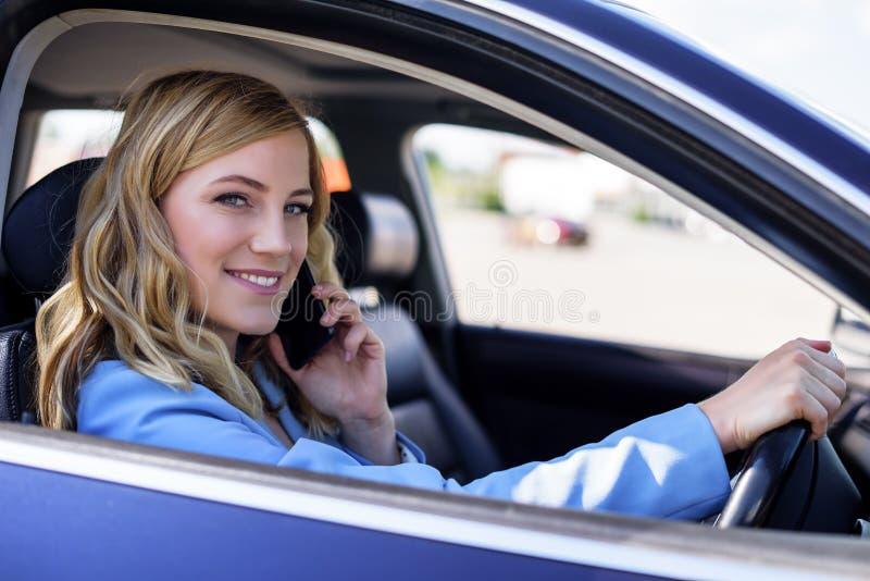 De vrouw spreekt op de telefoon in de auto royalty-vrije stock foto
