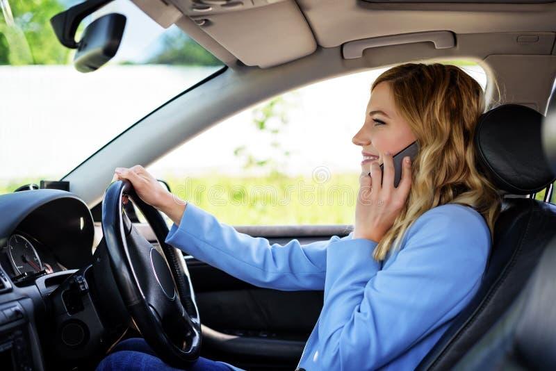 De vrouw spreekt op de telefoon in de auto stock foto