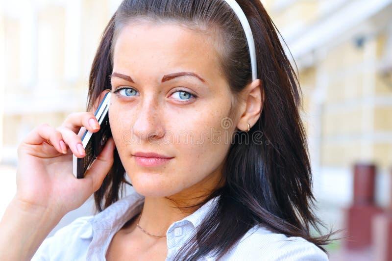 De vrouw spreekt telefoon bij straat stock fotografie