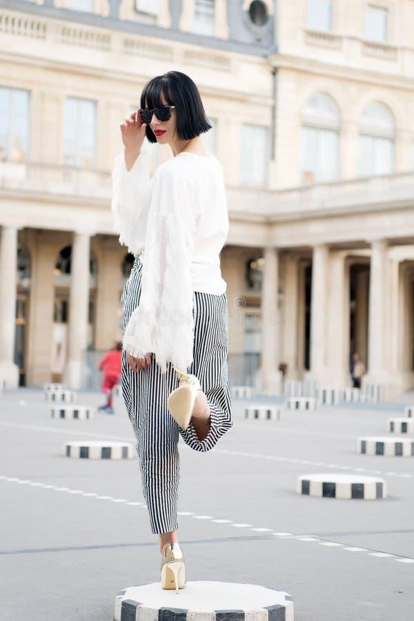 De vrouw stelt op hoge hielschoenen in Parijs, Frankrijk Sensuele vrouw met donkerbruin haar Het schoonheidsmeisje met glamour ki royalty-vrije stock foto's