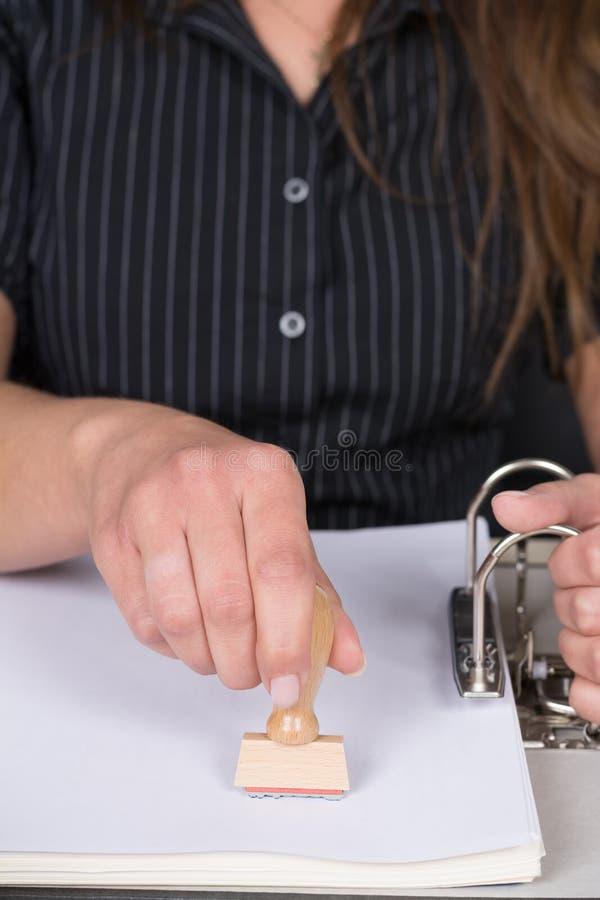 De vrouw stempelt een document met een zegel stock fotografie