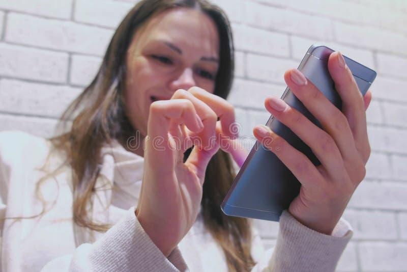 De vrouw stuurt een bericht op mobiel telefoonzitting en wachten somebody in koffie royalty-vrije stock afbeelding