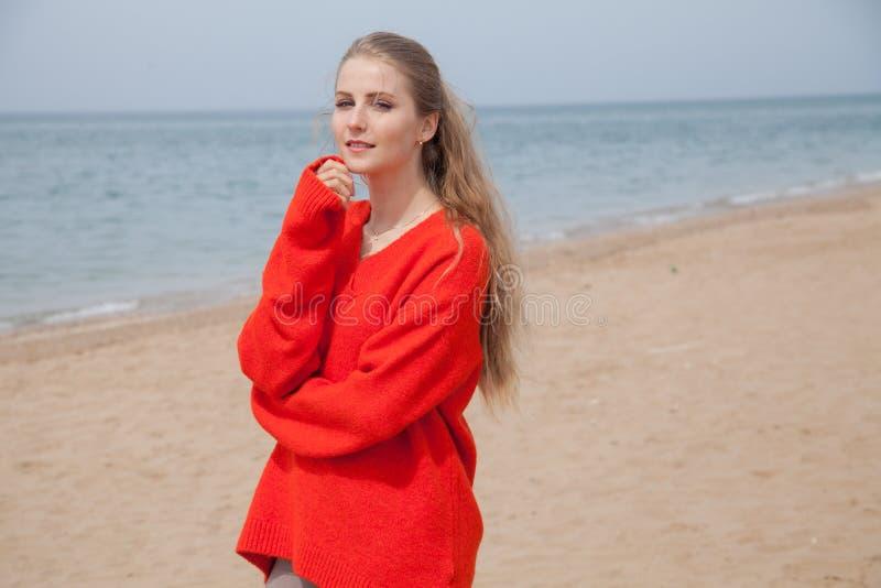 De vrouw in de Sweater die op zandig strand, één overzeese kust lopen stock foto