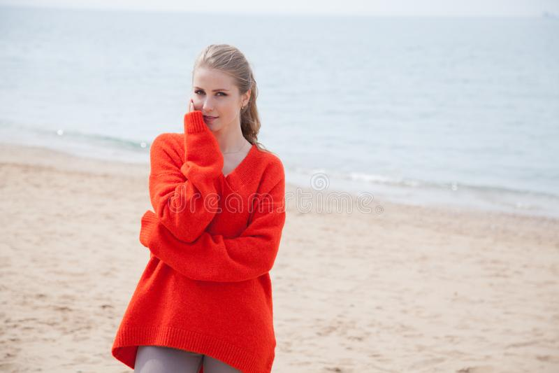 De vrouw in de Sweater die op zandig strand, één overzeese kust lopen stock afbeeldingen