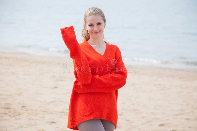 De vrouw in de Sweater die op zandig strand, één overzeese kust lopen royalty-vrije stock foto's