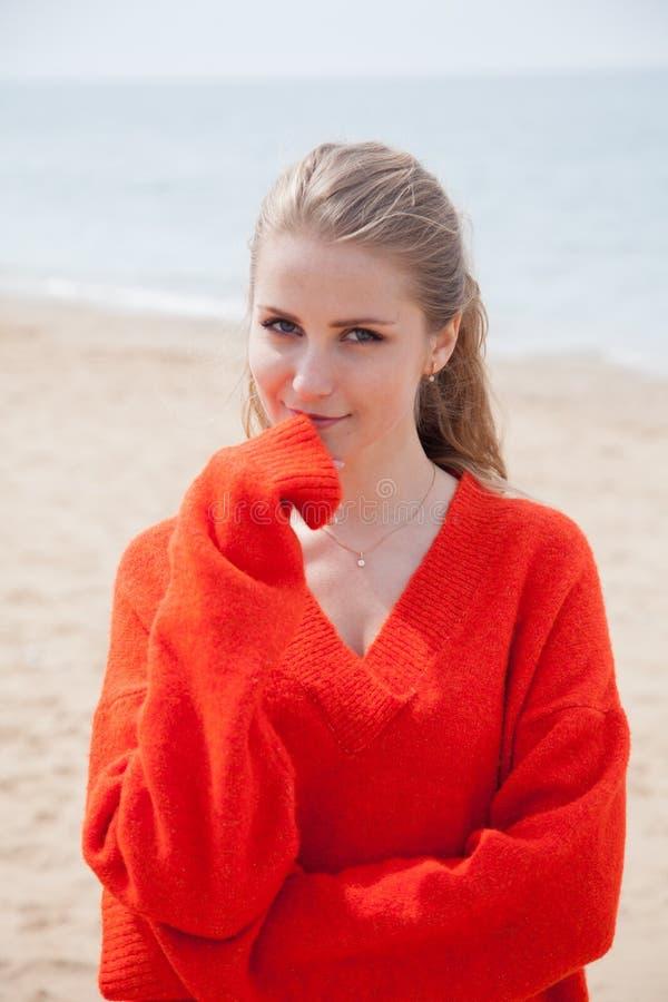 De vrouw in de Sweater die op zandig strand, één overzeese kust lopen royalty-vrije stock foto
