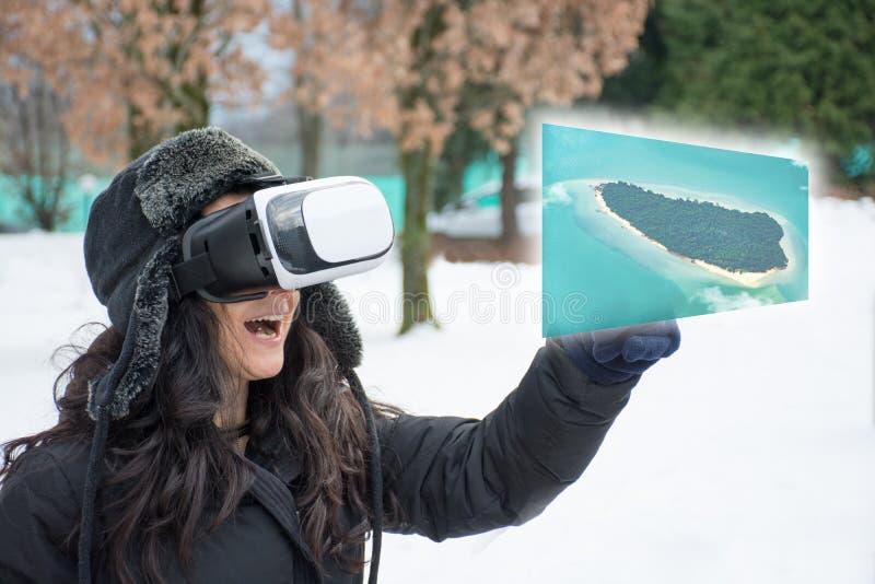 De vrouw tijdens de sneeuwwinter gebruikt virtuele werkelijkheidsglazen om een de zomer tropische overzees te zien royalty-vrije stock fotografie