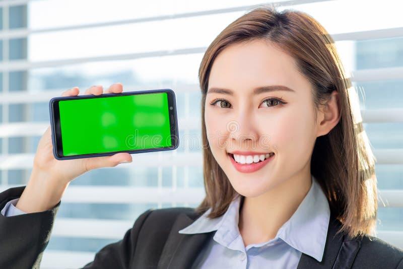 De vrouw toont het groene scherm van mobiel stock afbeeldingen