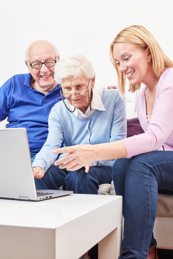 De vrouw toont oudsten bij de computer Internet stock afbeeldingen