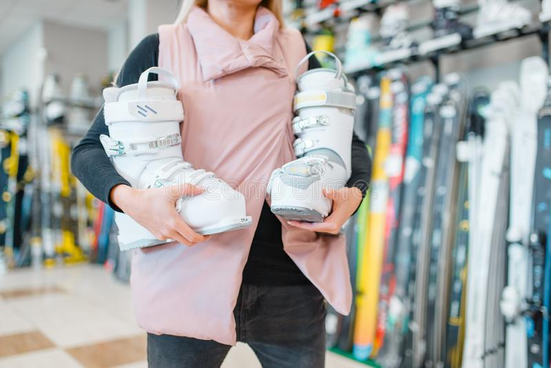 De vrouw toont ski of snowboarding laarzen, sportenwinkel royalty-vrije stock foto's