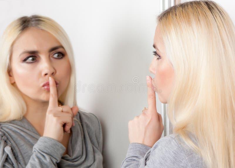 De vrouw toont stilteteken bekijkend haar gedachtengang in de spiegel stock foto
