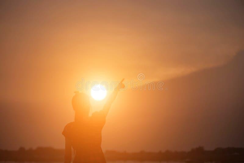 De vrouw toont de zonsondergangachtergrond van het handensilhouet stock foto's