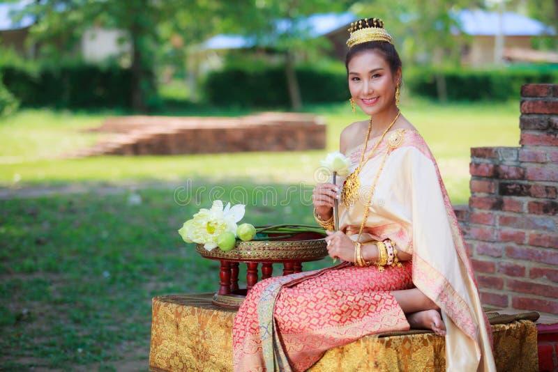 De vrouw in traditionele die kleren vouwt de bloemblaadjes van de lotusbloembloem in rituelen van Boeddhismegodsdienst worden geb royalty-vrije stock foto