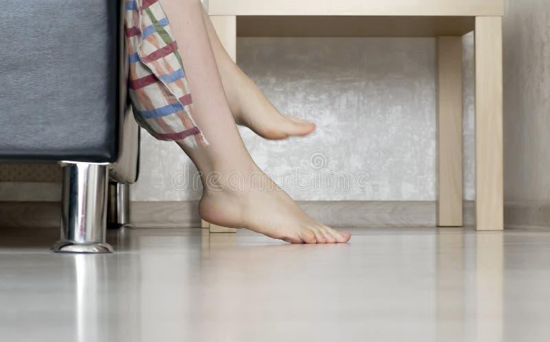 De vrouw trekt haar benen uit bed stock foto's