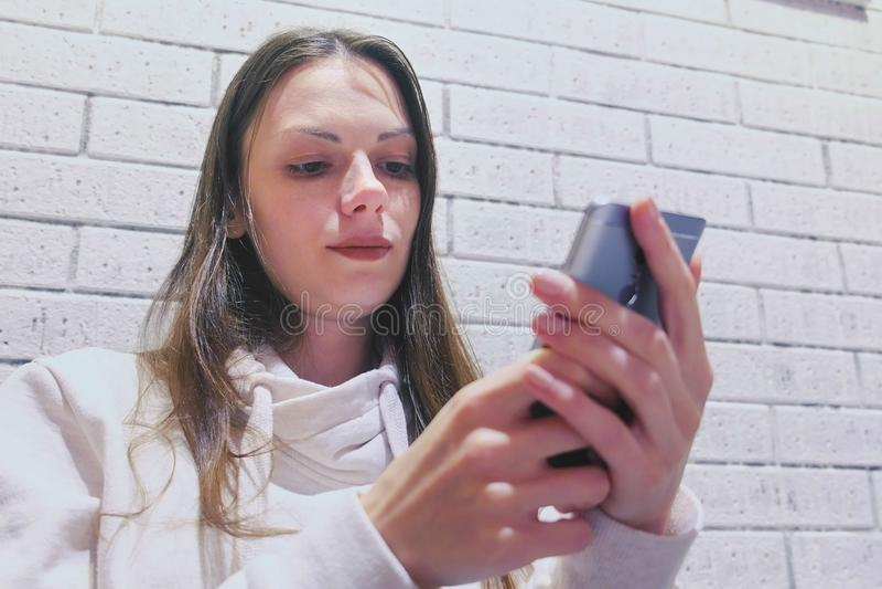 De vrouw typt een bericht op mobiel telefoonzitting en wachten somebody in koffie royalty-vrije stock afbeelding