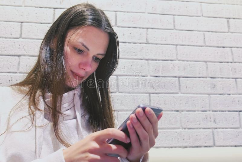 De vrouw typt een bericht op mobiel telefoonzitting en wachten somebody in koffie stock afbeeldingen