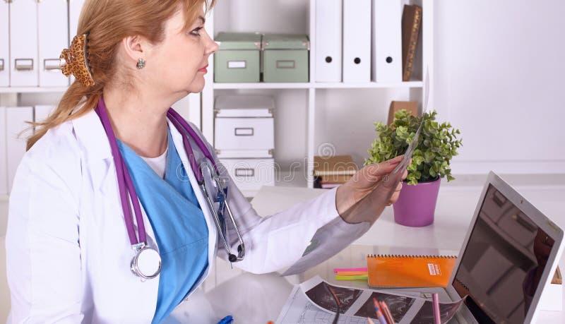 De vrouw van de arts bij het bureau in het bureau stock fotografie