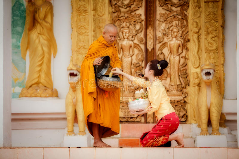 De vrouw van Beautufullaos om verdienste aan monniken van Boeddhisme te geven Dit l royalty-vrije stock fotografie