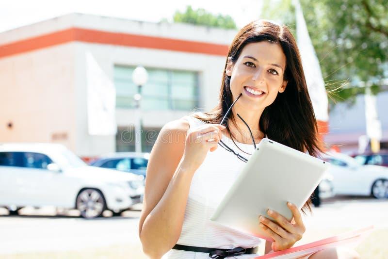 De vrouw van de autoverkoop met tablet in handel toont stock foto's