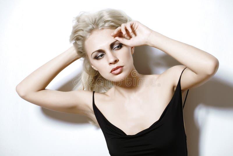 De vrouw van de blonde in een zwarte kleding. royalty-vrije stock afbeelding