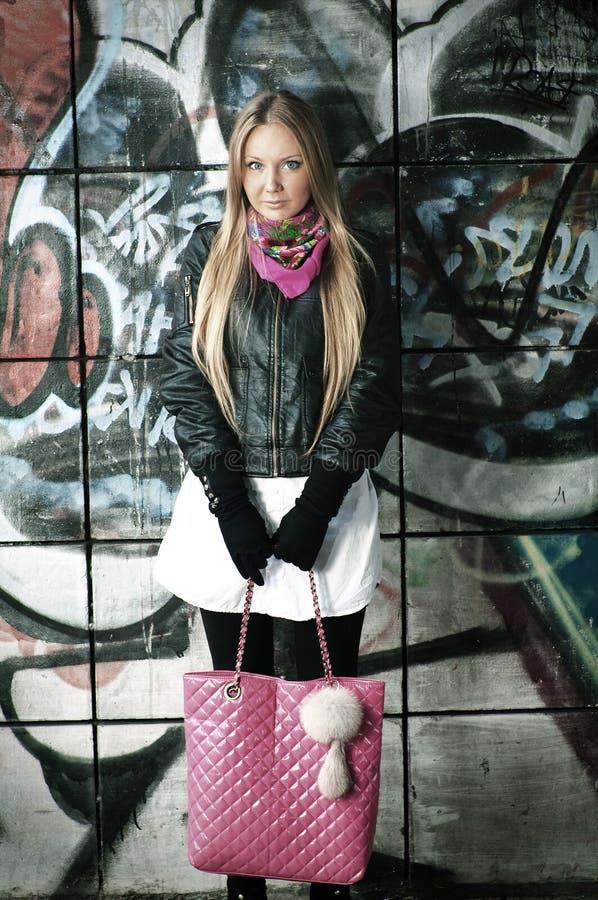 De vrouw van de blonde het stellen van graffiti stock afbeelding