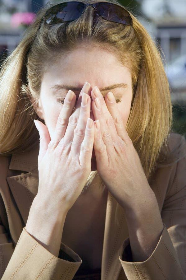 De vrouw van de blonde met hoofdpijn stock afbeeldingen