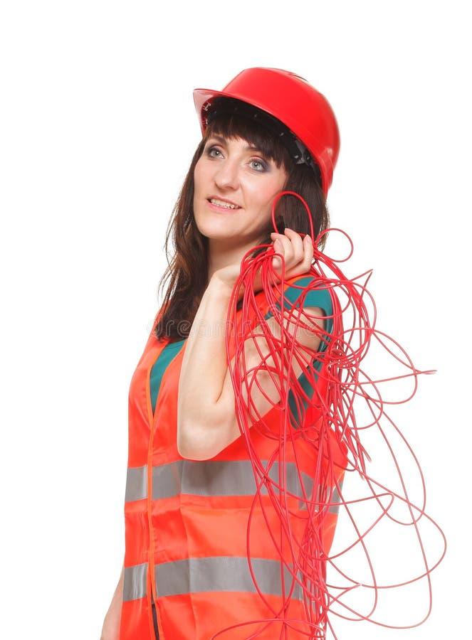 De vrouw van de bouwer in weerspiegelend vest met rode kabel royalty-vrije stock foto's