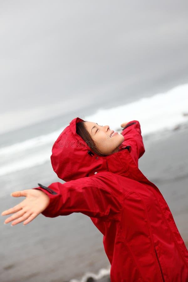 De vrouw van de daling in regen gelukkig door aardoceaan stock afbeelding
