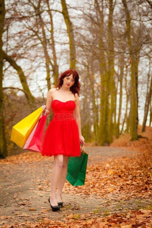De vrouw van de de herfstklant met verkoopzakken openlucht in park royalty-vrije stock afbeeldingen