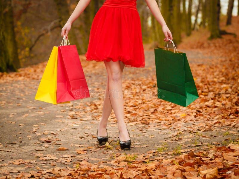 De vrouw van de de herfstklant met verkoopzakken openlucht in park stock afbeelding