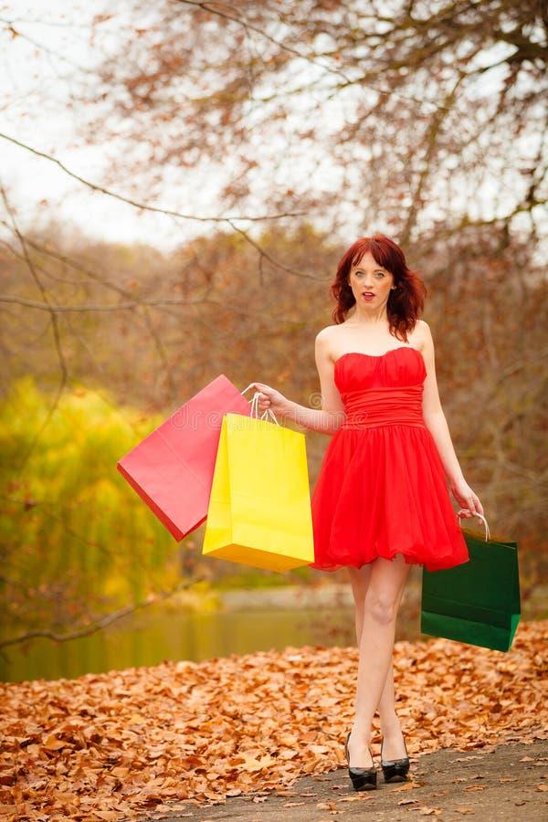 De vrouw van de de herfstklant met verkoopzakken openlucht in park stock foto