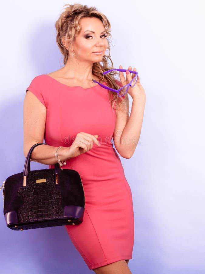 De vrouw van de DMaturemanier houdt handtas stock afbeeldingen