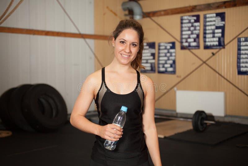De vrouw van de geschiktheid met een fles water stock foto's
