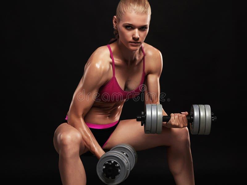 De vrouw van de geschiktheidsbodybuilder met domoren mooi blondemeisje met spieren royalty-vrije stock fotografie
