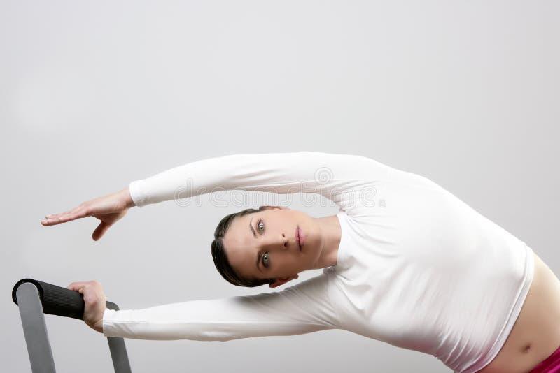De vrouw van de gymnastiek pilates het uitrekken zich sport in hervormerbed royalty-vrije stock afbeeldingen