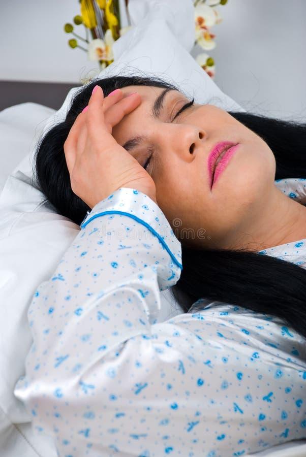 De vrouw van de hoofdpijn op bed royalty-vrije stock fotografie