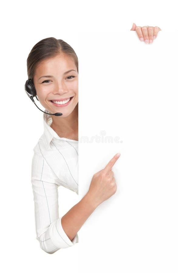 De vrouw van de hoofdtelefoon in call centre dat zich bij aanplakbord bevindt royalty-vrije stock afbeelding