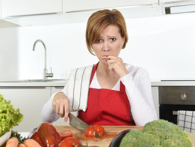 De vrouw van de huiskok in rode schort snijdende wortel met keukenmes die aan binnenlands ongevallenknipsel lijden die vinger kwe royalty-vrije stock afbeelding