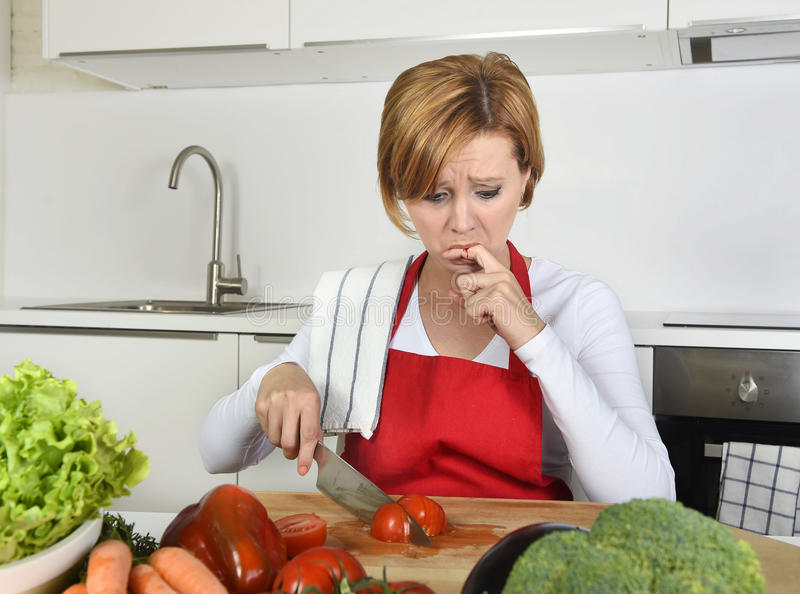 De vrouw van de huiskok in rode schort snijdende wortel met keukenmes die aan binnenlands ongevallenknipsel lijden die vinger kwe royalty-vrije stock fotografie